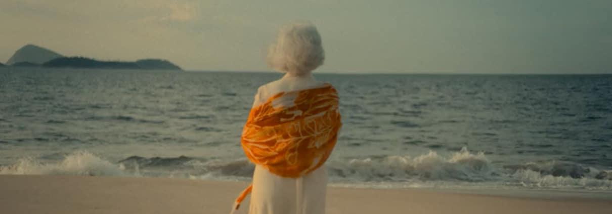 Weißhaarige ältere Dame steht mit dem Rücken zur Kamera in Abendstimmung am Meeresstrand. Am Horizont eine Insel.
